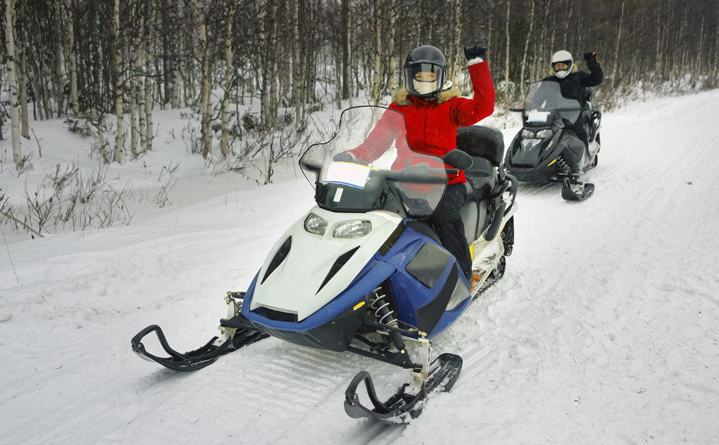 Woman and Man managing snowmobile in Ruka in Lapland